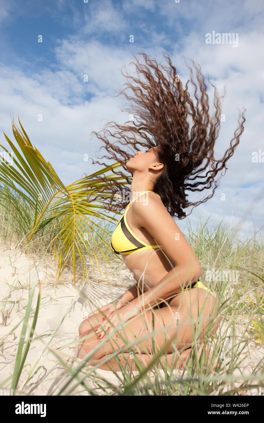 beautiful girl swaying her hair on beach. - Stock Image