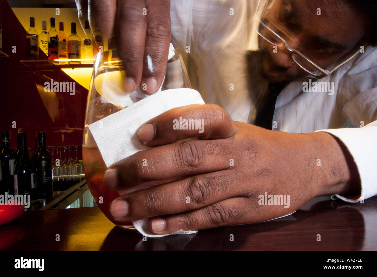 Man making a juice on wooden table, inside at a hotel, colorized photograph including perfect lights, very tasty cool drink of luxury restaurant. - Stock Image