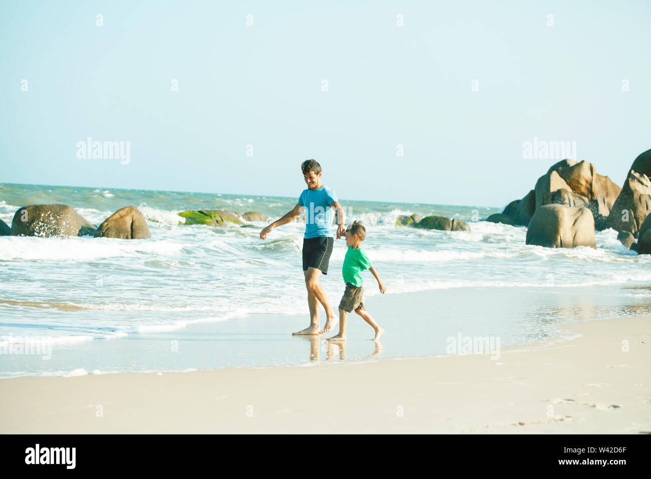 happy family on beach playing, father with son walking sea coast, rocks behind smiling taking vacation closeup - Stock Image