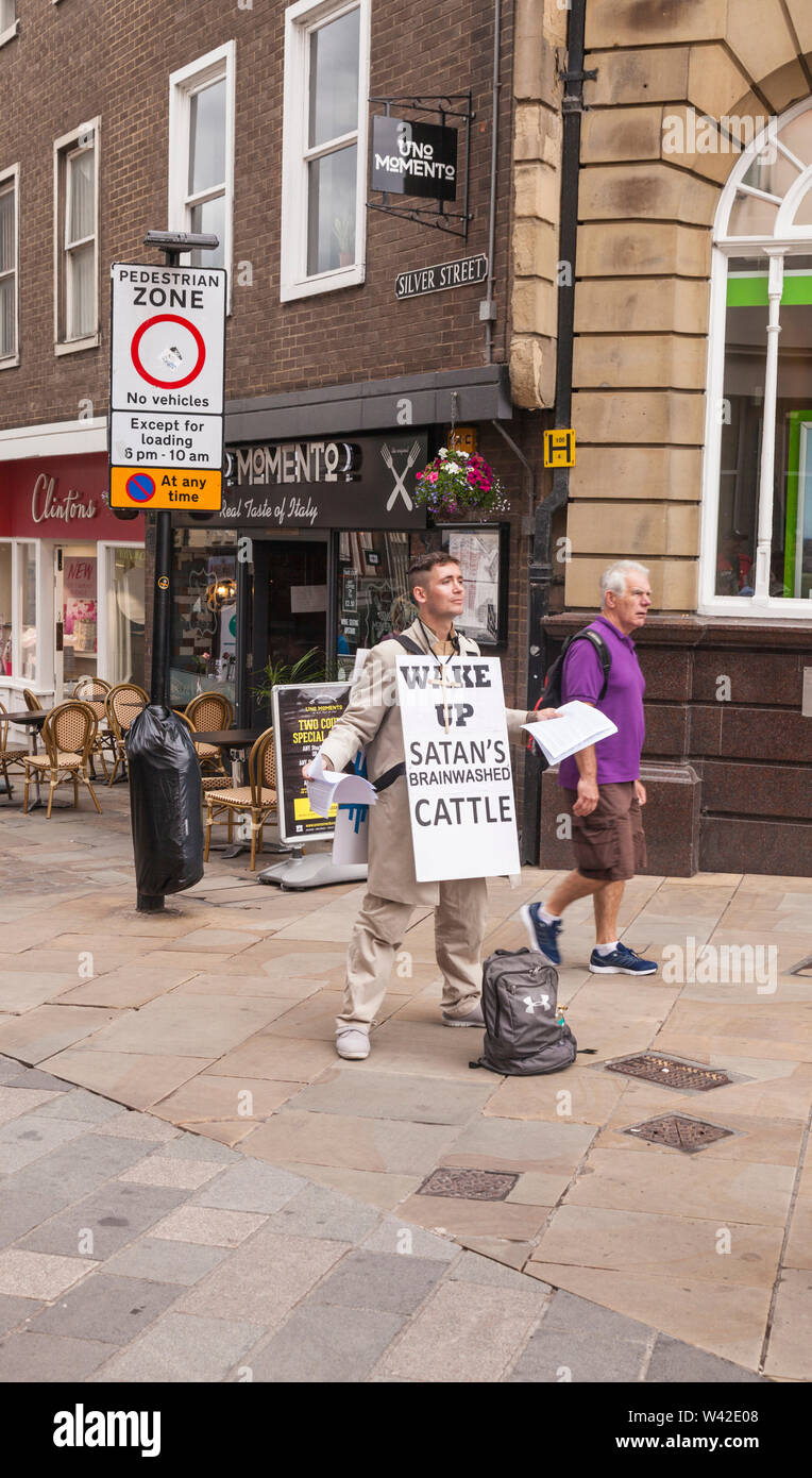 A man wearing a sandwichboard notice in the centre of Durham,England,UK stating, 'Wake Up,Satans Brainwashed Cattle' - Stock Image