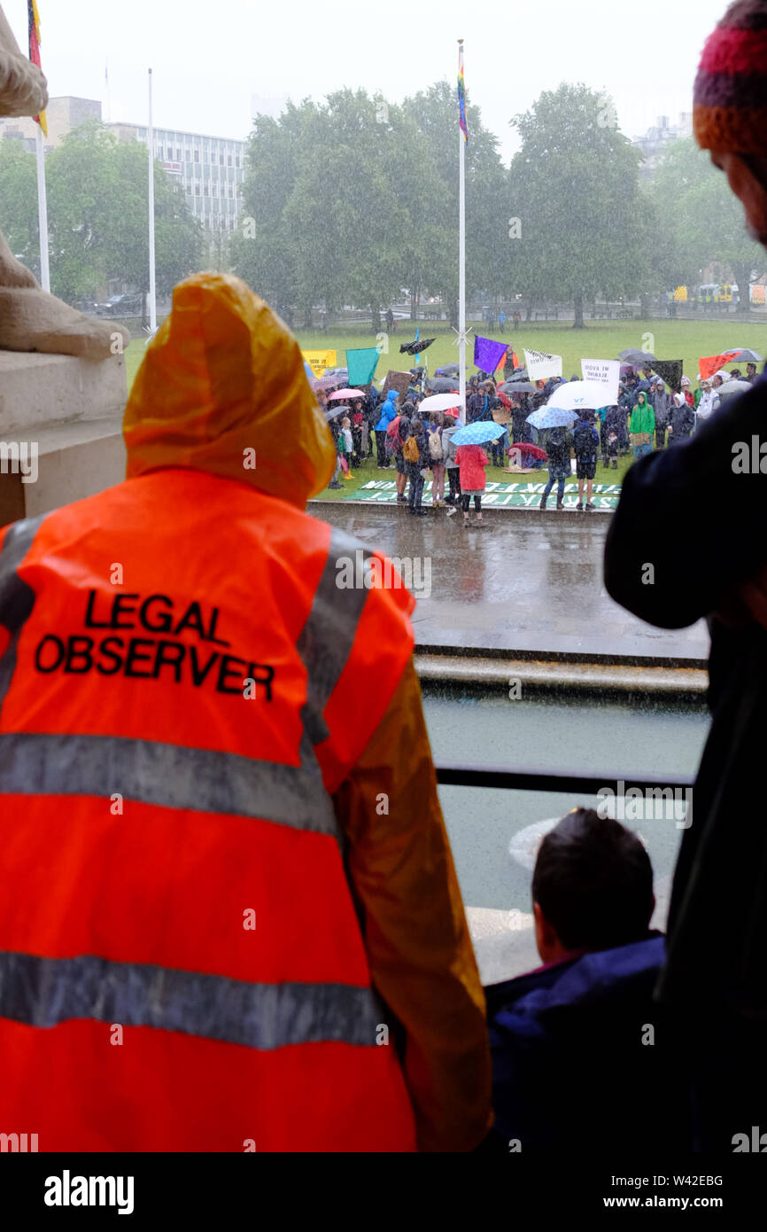 Bristol, UK. 19th July 2019. Rain pours on the Extinction Rebellion youth rally on college Green in Bristol City center. This is the 5th day of the climate change protest in the city. A legal observer watches from the shelter of the council house. Credit: Mr Standfast/Alamy Live News Stock Photo