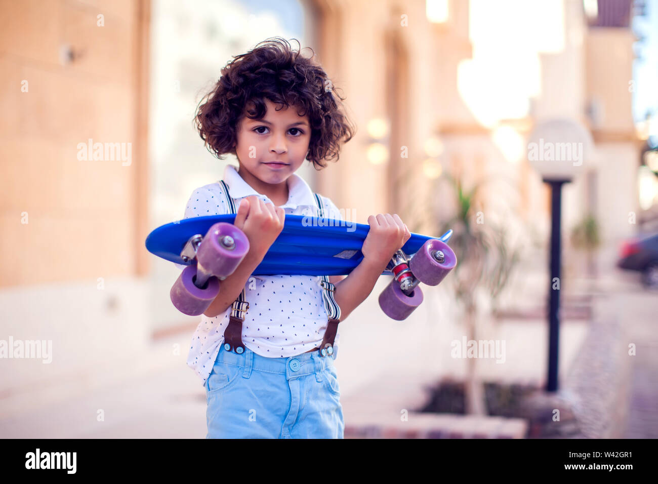 Little Boy With Curly Hair With Skateboard Outdoor Children And Entertainment Concept Stock Photo Alamy