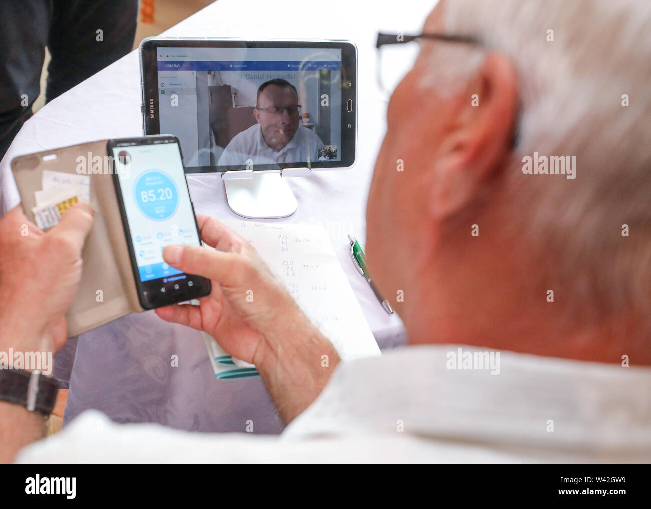 19 July 2019, Saxony-Anhalt, Halle (Saale): Pensioner Norbert Neumann talks about a video call via tablet with his family doctor. From the point of view of a housing cooperative in Halle, telemedicine could be a great help, especially for older people. In a project in 20 apartments, 94 percent of the test persons rated the digital doctor's interview as very good or good. For the 'Haendel II' project, 20 apartments were equipped with the appropriate technology. Subjects were able to reach a doctor via tablet. Photo: Jan Woitas/dpa-Zentralbild/dpa - Stock Image