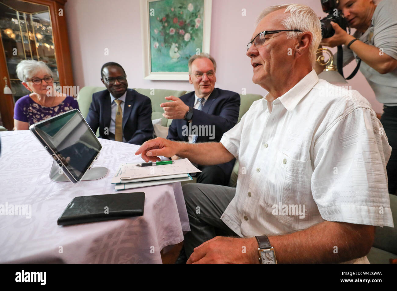 19 July 2019, Saxony-Anhalt, Halle (Saale): Pensioner Siglinde Neumann (l-r), Karamba Diaby (SPD), Member of the Bundestag for Halle (Saale), Reiner Haseloff (CDU), Prime Minister of Saxony-Anhalt, and pensioner Norbert Neumann talk about the advantages of telemedicine at a media event. From the point of view of a housing cooperative in Halle, telemedicine could be a great help, especially for older people. In a project in 20 apartments, 94 percent of the test persons rated the digital doctor's interview as very good or good. For the 'Haendel II' project, 20 apartments were equipped with the a - Stock Image