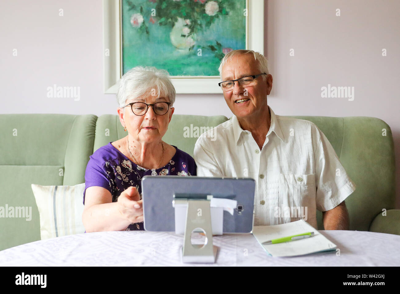 19 July 2019, Saxony-Anhalt, Halle (Saale): The pensioners Siglinde and Norbert Neumann use a tablet for communication with their family doctor. From the point of view of a housing cooperative in Halle, telemedicine could be a great help, especially for older people. In a project in 20 apartments, 94 percent of the test persons rated the digital doctor's interview as very good or good. For the 'Haendel II' project, 20 apartments were equipped with the appropriate technology. Subjects were able to reach a doctor via tablet. Photo: Jan Woitas/dpa-Zentralbild/dpa - Stock Image
