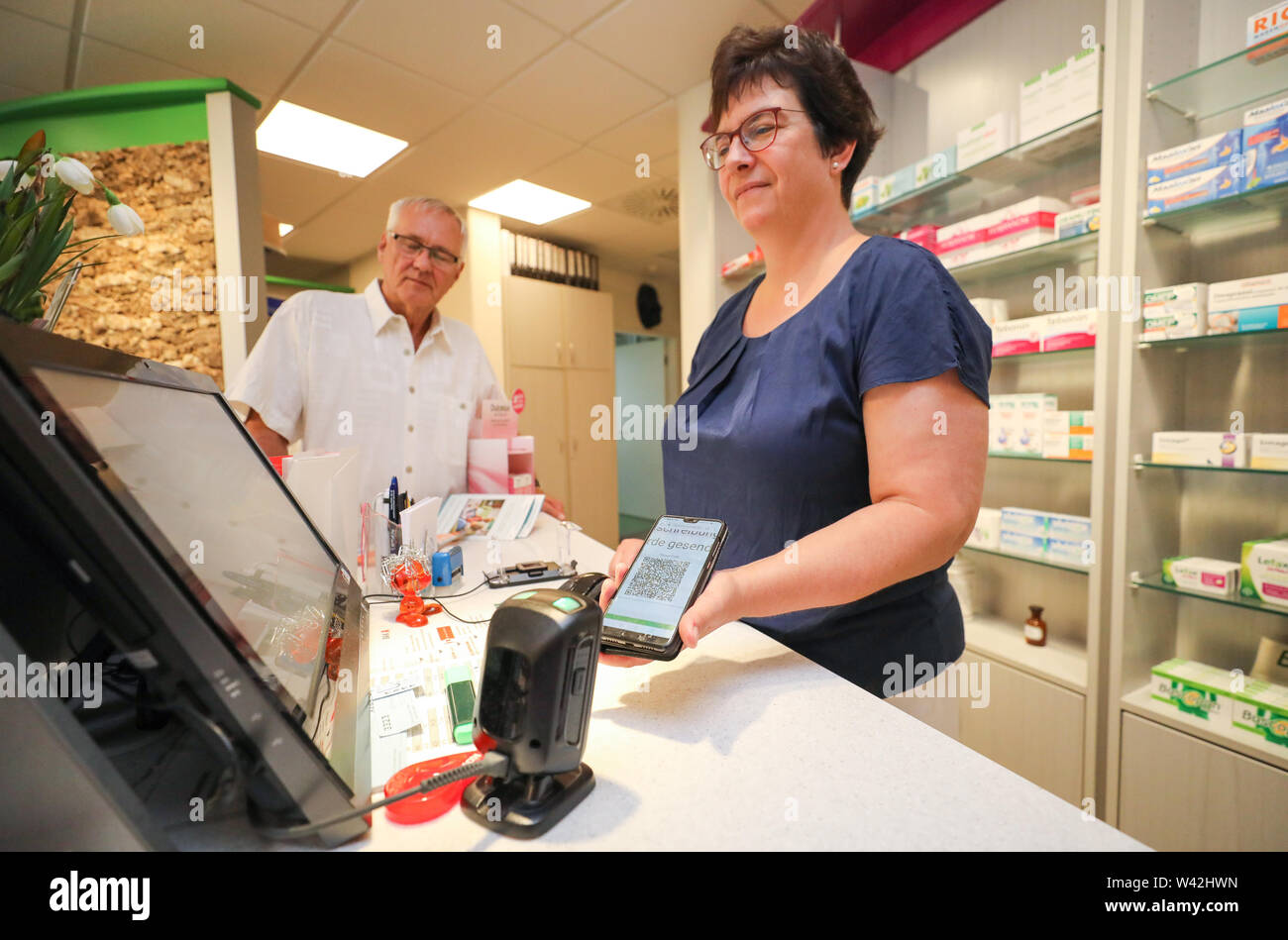 19 July 2019, Saxony-Anhalt, Halle (Saale): Pharmacist Ursula Gütle scans the code for the digital prescription from Norbert Neumann's mobile phone. From the point of view of a housing cooperative in Halle, telemedicine could be a great help, especially for older people. In a project in 20 apartments, 94 percent of the test persons rated the digital doctor's interview as very good or good. For the 'Haendel II' project, 20 apartments were equipped with the appropriate technology. Subjects were able to reach a doctor via tablet. Photo: Jan Woitas/dpa-Zentralbild/dpa - Stock Image