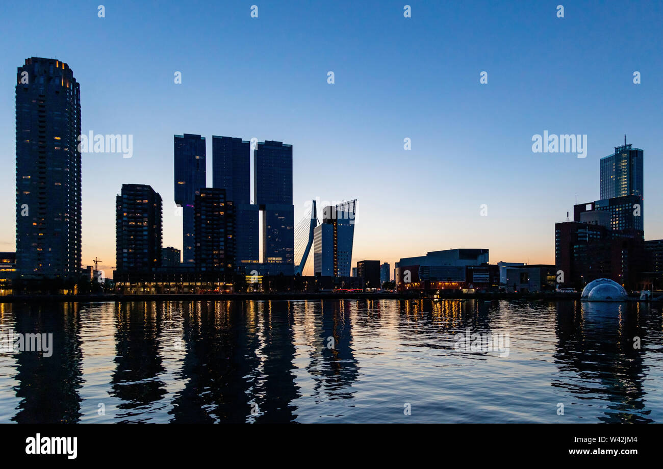 Rotterdam skyline night view. City towers illuminated, reflections on the river Maas water, sunset time, blue clear sky, summer evening - Stock Image