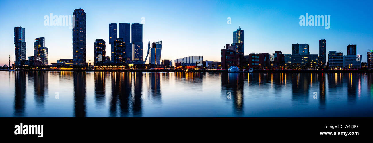 Rotterdam skyline night panoramic view. City towers illuminated panorama, reflections on the river Maas water, sunset time, blue clear sky, summer eve - Stock Image