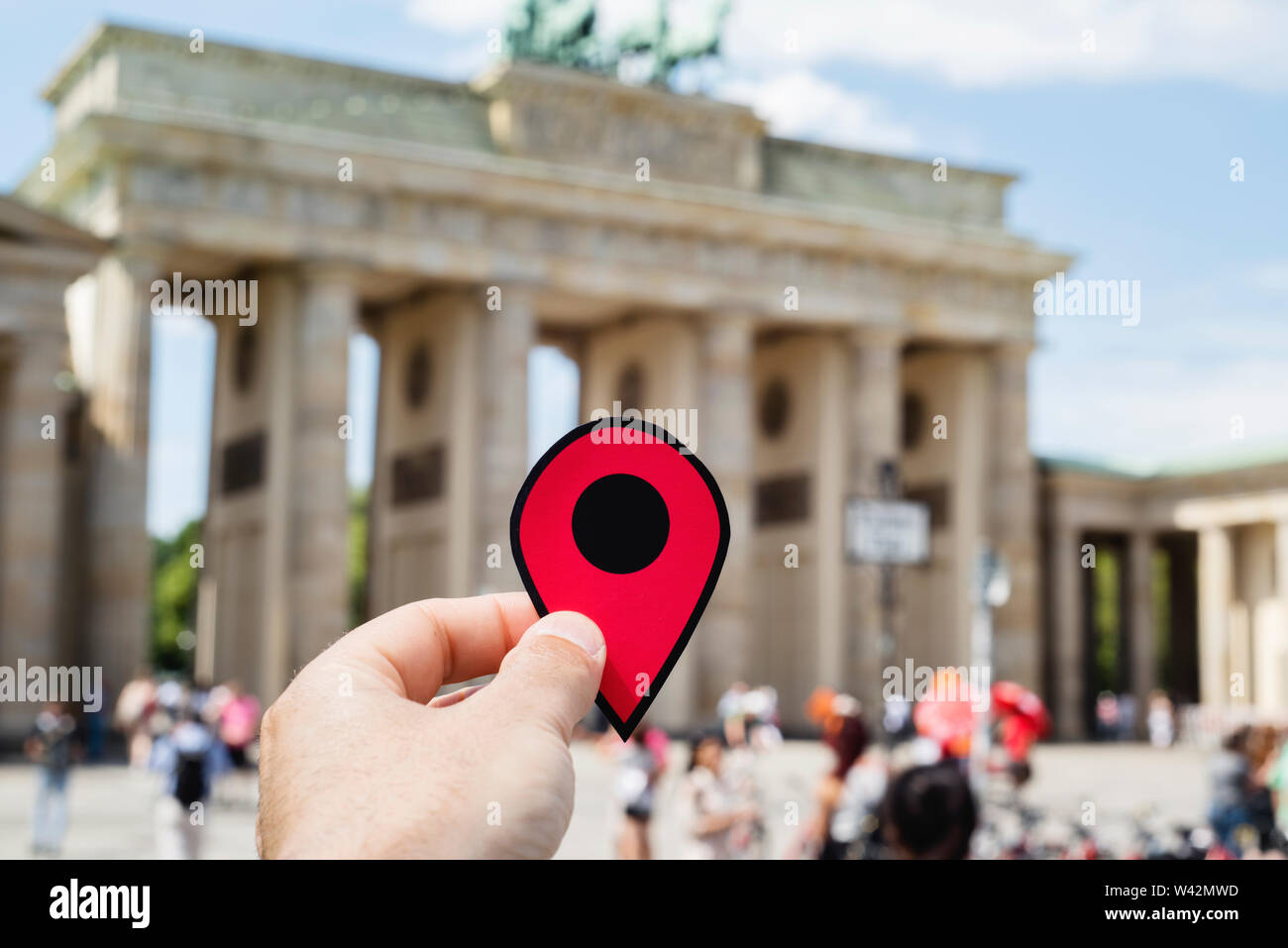 closeup of the hand of a young caucasian man with a red marker in the popular Brandenburg Gate in Berlin, Germany - Stock Image