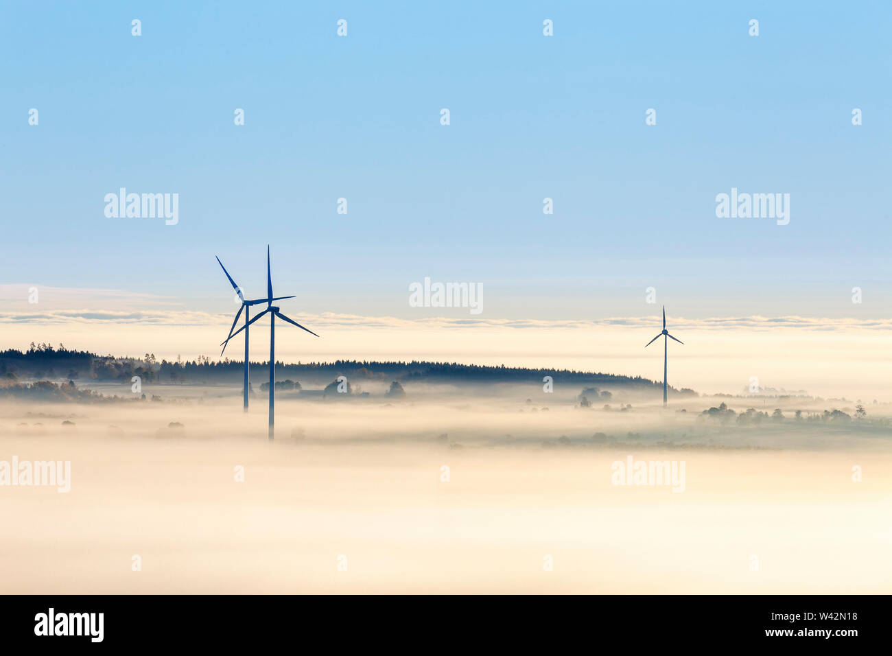 Wind turbines in morning fog Stock Photo