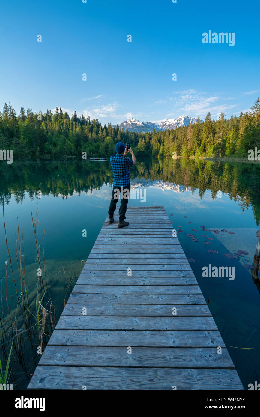 Man on platform taking photos at Cresta lake (Crestasee) with smartphone, Flims, canton of Graubunden, Switzerland - Stock Image