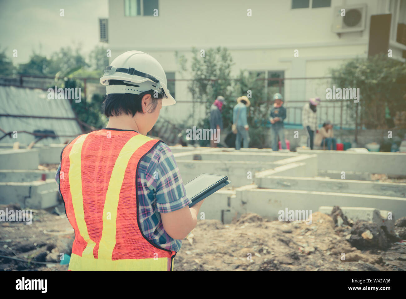 Asian women engineering holds a tablet for use in the inspection of construction sites for accuracy and in accordance with the plan. Concept of Equal Stock Photo