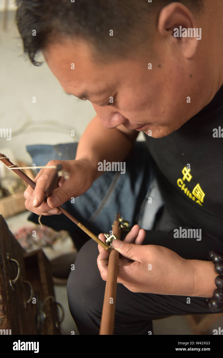(190719) -- QINGDAO, July 19, 2019 (Xinhua) -- Sun Lianyong, a steelyard craftsman, drills the beam of a steelyard at his workshop in Jinkou Town of Jimo District in Qingdao, east China's Shandong Province, July 19, 2019. Steelyard, a traditional weighing instrument with a long history, used to be popular for its low cost and good portability. In the early 1990s, there used to be more than 30 steelyard workshops in Jimo as the development of market economy pushed up people's demand for steelyards.   The 49-year-old craftsman Sun Lianyong is an inheritor of traditional steelyard making techniqu - Stock Image
