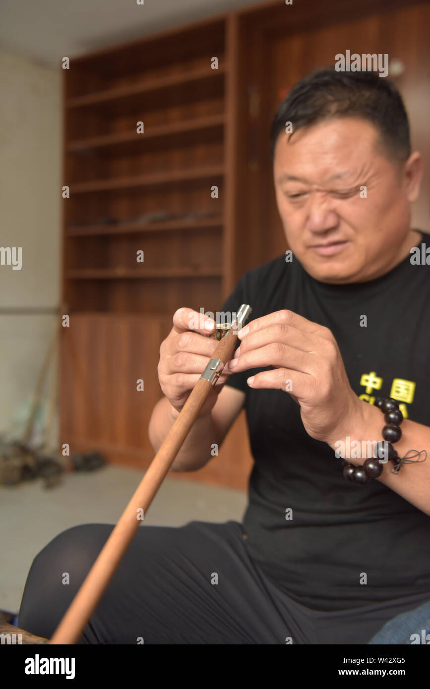 (190719) -- QINGDAO, July 19, 2019 (Xinhua) -- Sun Lianyong, a steelyard craftsman, makes a steelyard at his workshop in Jinkou Town of Jimo District in Qingdao, east China's Shandong Province, July 19, 2019. Steelyard, a traditional weighing instrument with a long history, used to be popular for its low cost and good portability. In the early 1990s, there used to be more than 30 steelyard workshops in Jimo as the development of market economy pushed up people's demand for steelyards. The 49-year-old craftsman Sun Lianyong is an inheritor of traditional steelyard making techniques. As the fi - Stock Image