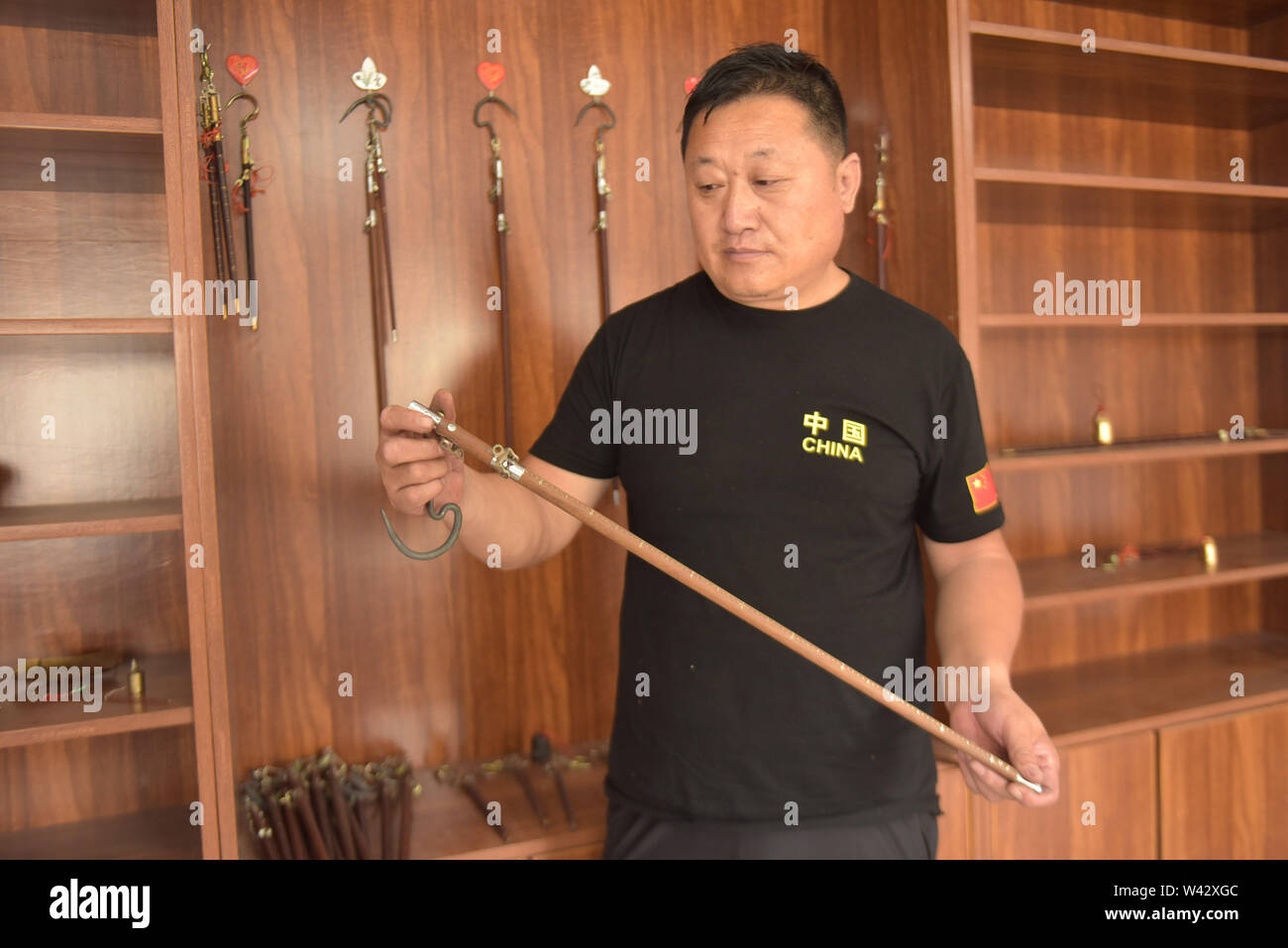 (190719) -- QINGDAO, July 19, 2019 (Xinhua) -- Sun Lianyong, a steelyard craftsman, shows a newly-made steelyard at his workshop in Jinkou Town of Jimo District in Qingdao, east China's Shandong Province, July 19, 2019. Steelyard, a traditional weighing instrument with a long history, used to be popular for its low cost and good portability. In the early 1990s, there used to be more than 30 steelyard workshops in Jimo as the development of market economy pushed up people's demand for steelyards.   The 49-year-old craftsman Sun Lianyong is an inheritor of traditional steelyard making techniques - Stock Image