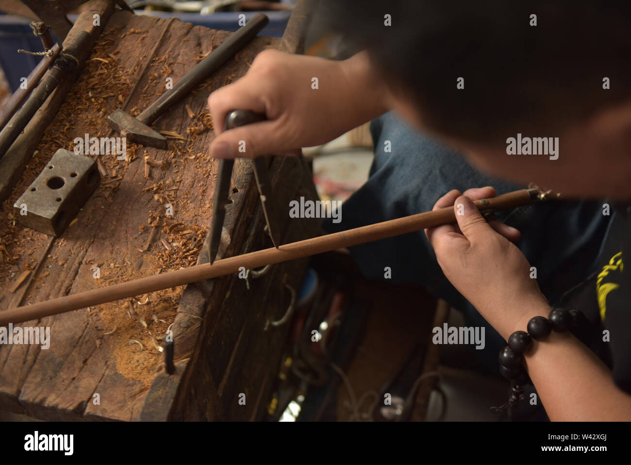 (190719) -- QINGDAO, July 19, 2019 (Xinhua) -- Sun Lianyong, a steelyard craftsman, processes the beam of a steelyard at his workshop in Jinkou Town of Jimo District in Qingdao, east China's Shandong Province, July 19, 2019. Steelyard, a traditional weighing instrument with a long history, used to be popular for its low cost and good portability. In the early 1990s, there used to be more than 30 steelyard workshops in Jimo as the development of market economy pushed up people's demand for steelyards.   The 49-year-old craftsman Sun Lianyong is an inheritor of traditional steelyard making techn - Stock Image