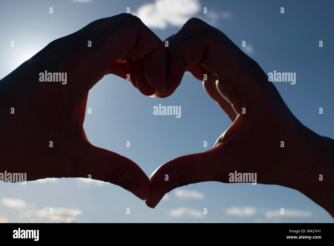 Sunset in heart hands on sky - Stock Image