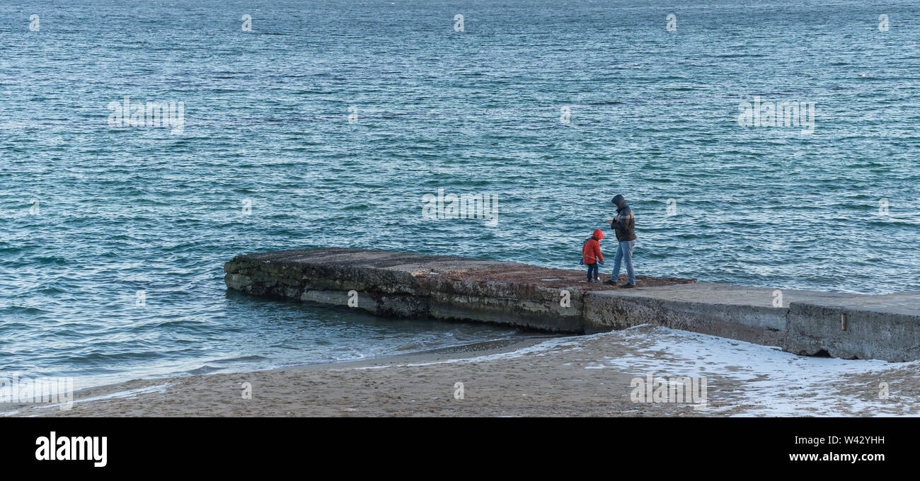 Odessa, Ukraine - 12.27.2018. Lonely people on the pier by the sea on a sunny winter day - Stock Image
