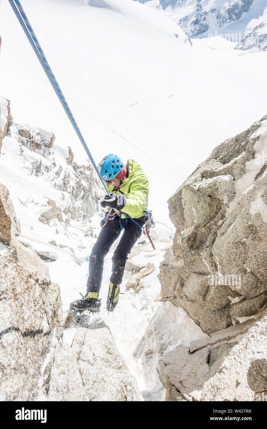Alpinist rappelling steep terrain high above a Mont Blanc glacier Stock Photo