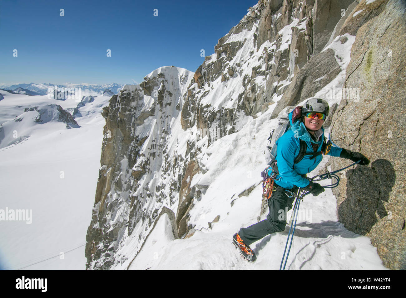 Woman alpinist smiles while managing ropes on the Cosmiques Ridge Stock Photo