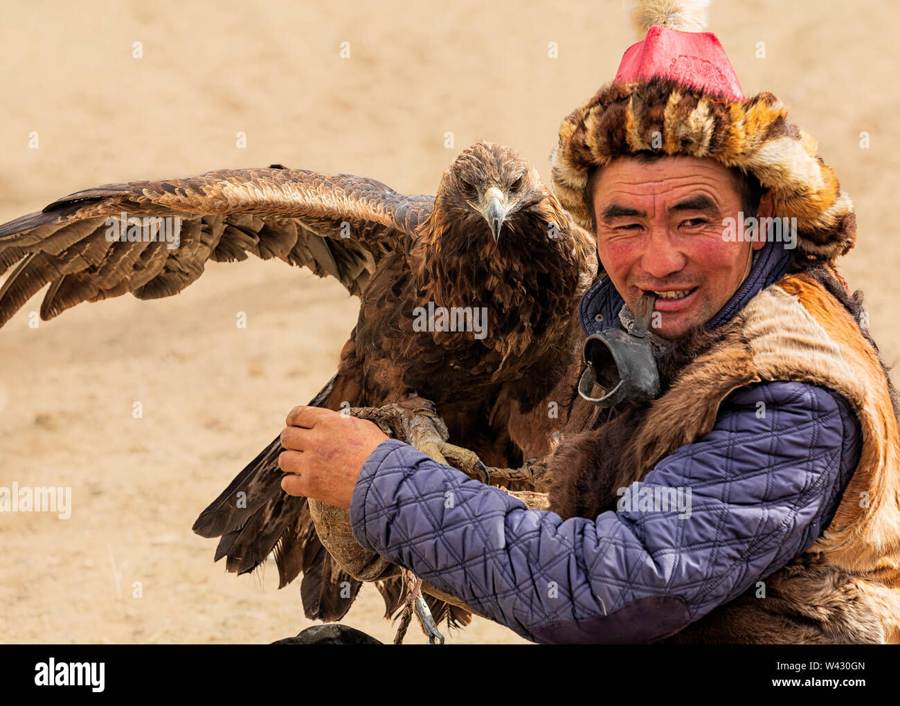 Bayan-Ulgii, Western Mongolia - October 07, 2018: Nomad Games, Golden Eagle Festival. Sunny Day. Mongolian Hunter is sitting With Golden Eagle On hand Stock Photo