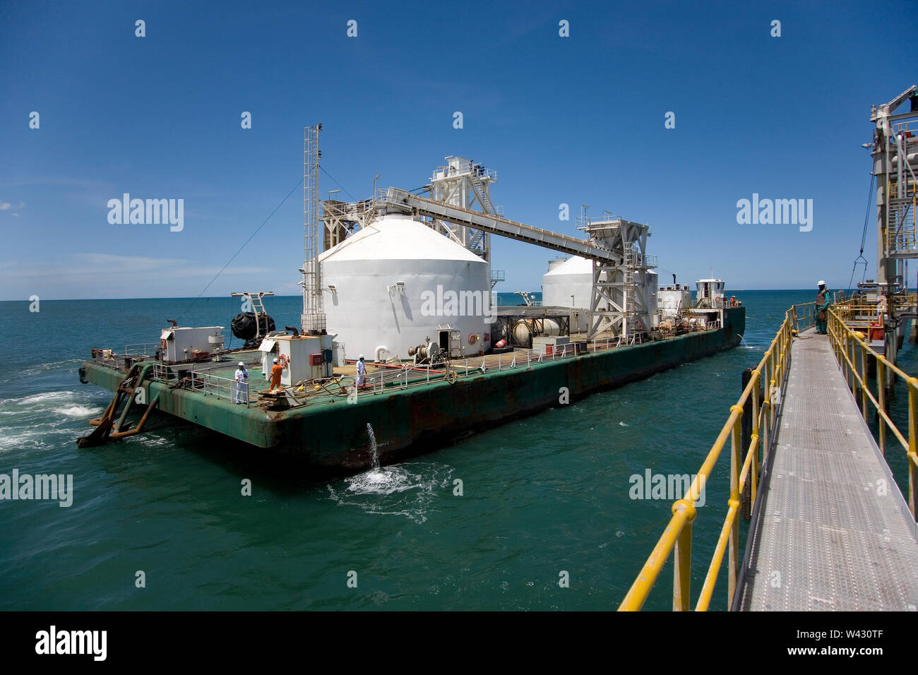 Mining, managing & transporting of titanium mineral sands. Custom built barge arriving at jetty to load up with mineral before transfer to OGV at sea. Stock Photo