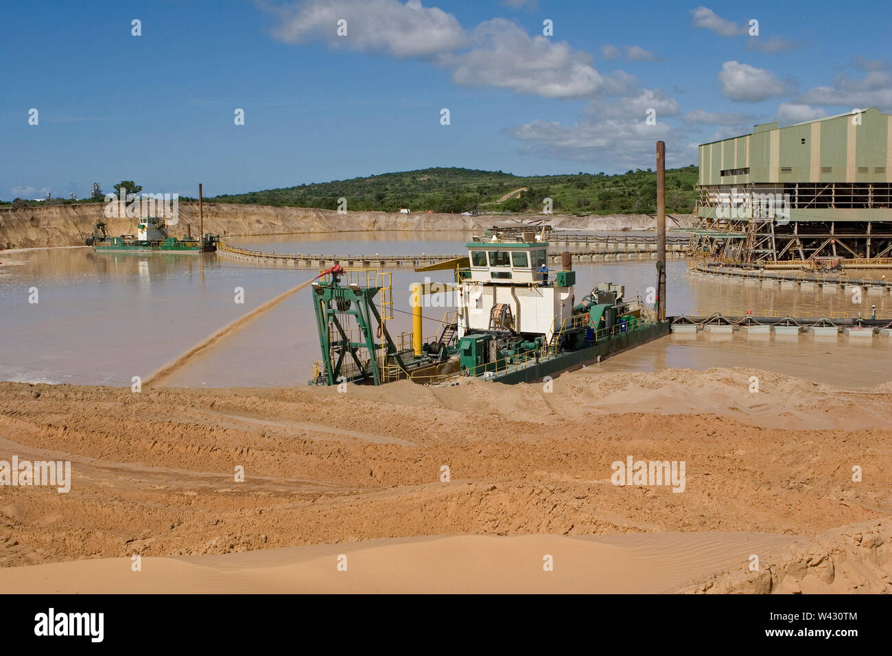 Managing & transporting of titanium mineral sands at mine site. Mining by dredging in freshwater ponds. Dredges pump sand into wet concentrator plant. Stock Photo