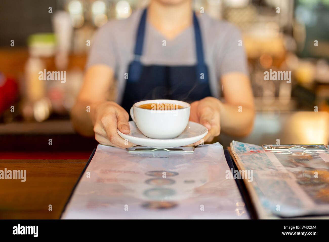 Waitress serving coffee while standing in coffee shop counter. - Stock Image