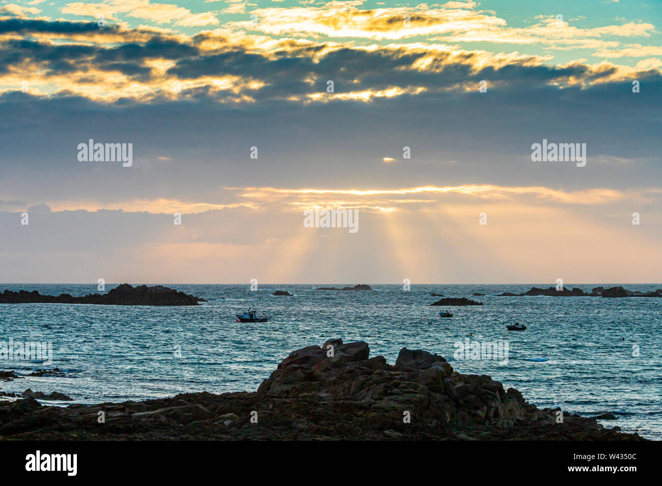The sun setting over Cobo Bay, Guernsey, Channel Islands UK Stock Photo