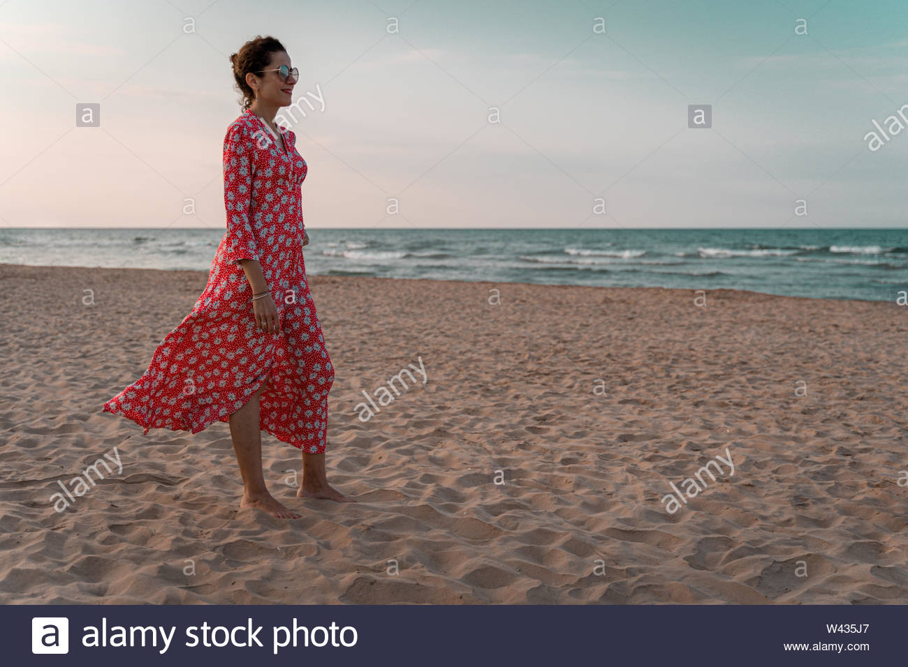 Beautiful woman in red dress looking to the mediterranean sea at sunset - Stock Image
