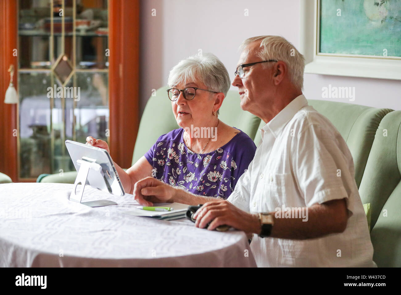 19 July 2019, Saxony-Anhalt, Halle (Saale): The pensioners Siglinde and Norbert Neumann use a tablet for communication with their family doctor. From the point of view of a housing cooperative in Halle, telemedicine could be a great help, especially for older people. In a project in 20 apartments, 94 percent of the test persons rated the digital doctor's interview as very good or good. For the 'Haendel II' project, 20 apartments were equipped with the appropriate technology. Subjects were able to reach a doctor via tablet. In addition, the apartments were equipped with sensors to detect critic - Stock Image