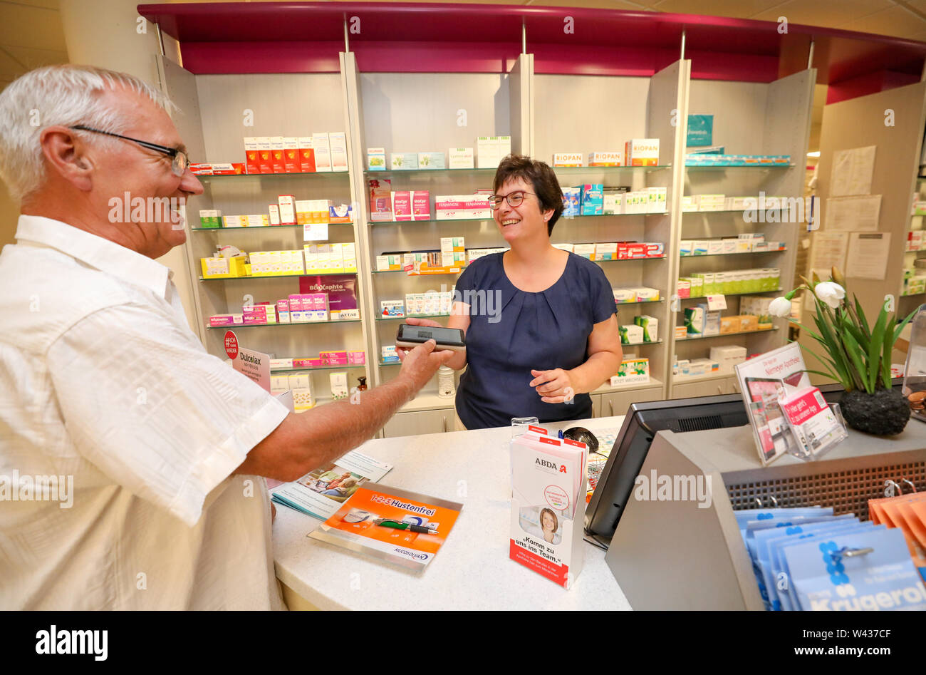 19 July 2019, Saxony-Anhalt, Halle (Saale): Pharmacist Ursula Gütle takes over the mobile phone of pensioner Norbert Neumann with the code for the digital prescription. From the point of view of a housing cooperative in Halle, telemedicine could be a great help, especially for older people. In a project in 20 apartments, 94 percent of the test persons rated the digital doctor's interview as very good or good. For the 'Haendel II' project, 20 apartments were equipped with the appropriate technology. Subjects were able to reach a doctor via tablet. In addition, the apartments were equipped with - Stock Image