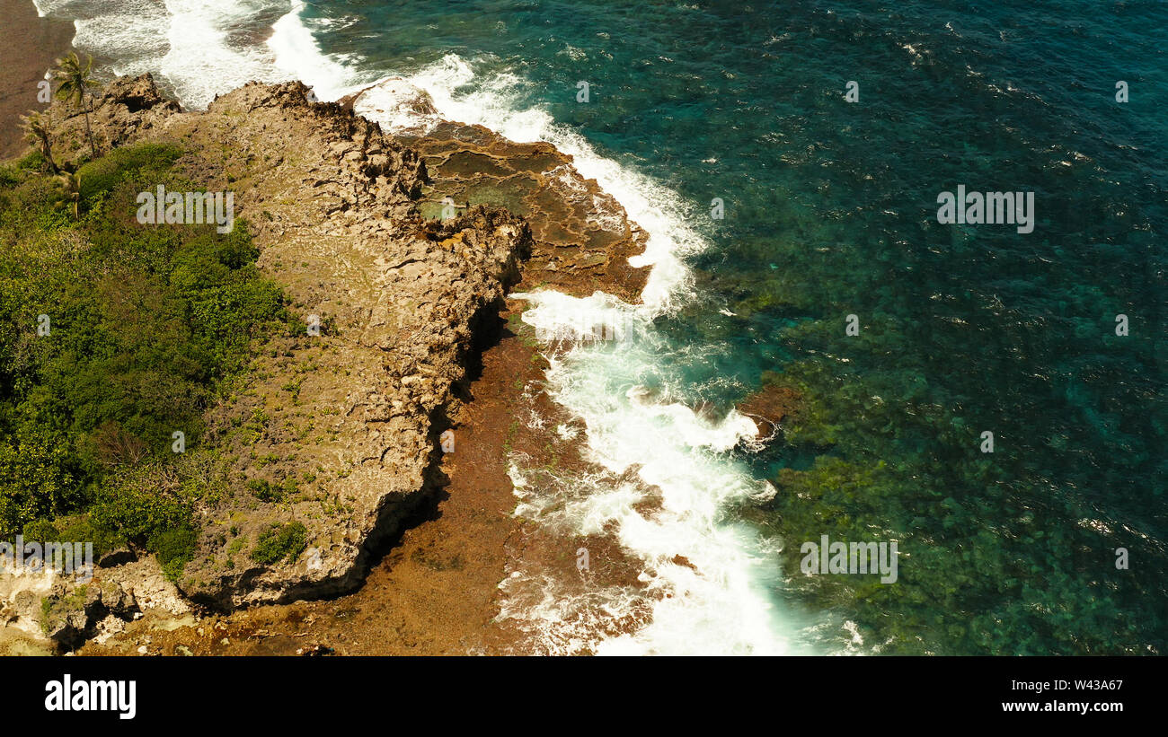 Ocean waves crashing on rocky shore from above. Siargao, Philippines. Summer and travel vacation concept Stock Photo