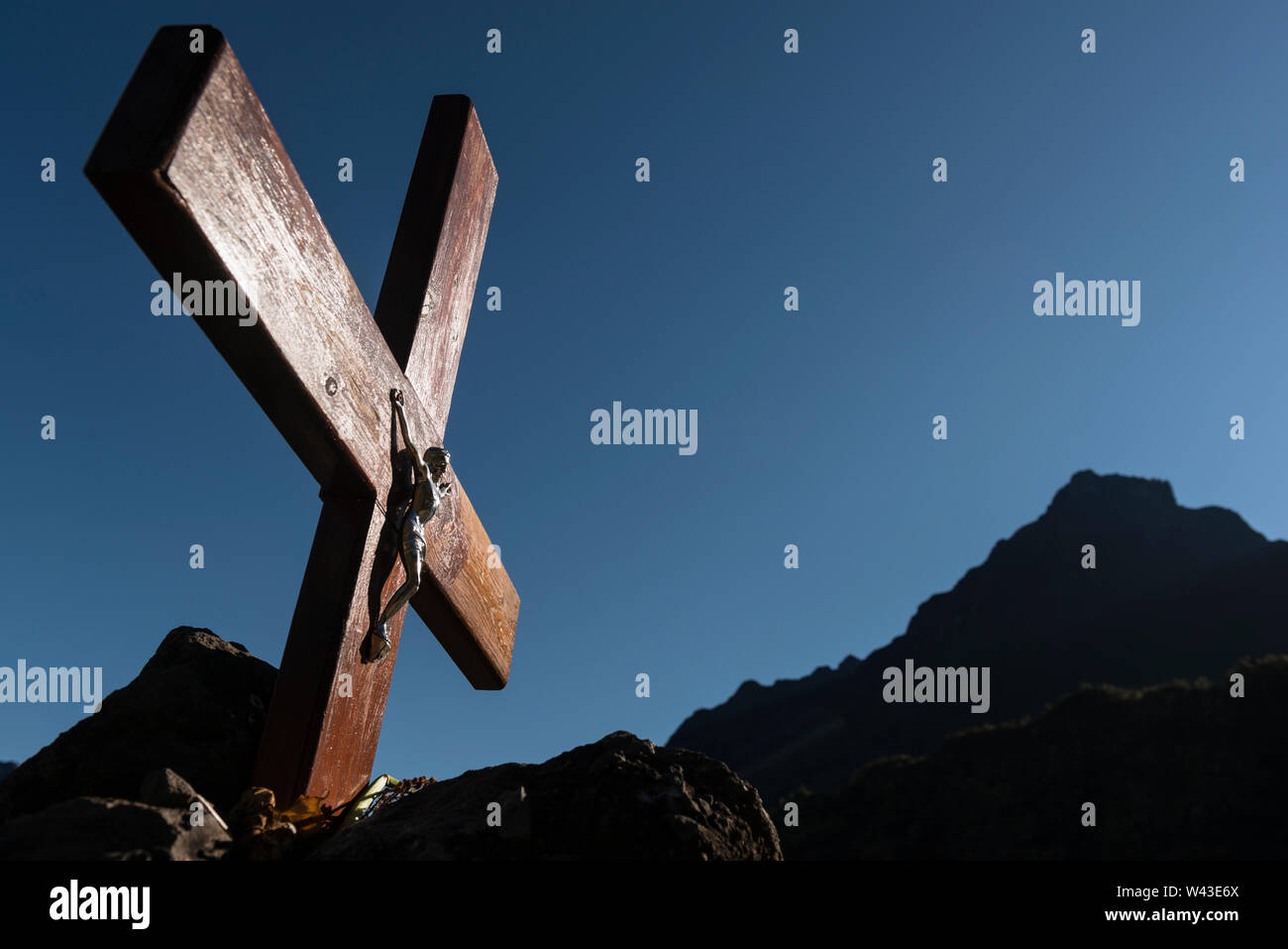 A large wooden crucifix outside the Catholic church, Marla village, early morning light. In background, caldera slopes of Cirque de Mafate, La Reunion Stock Photo