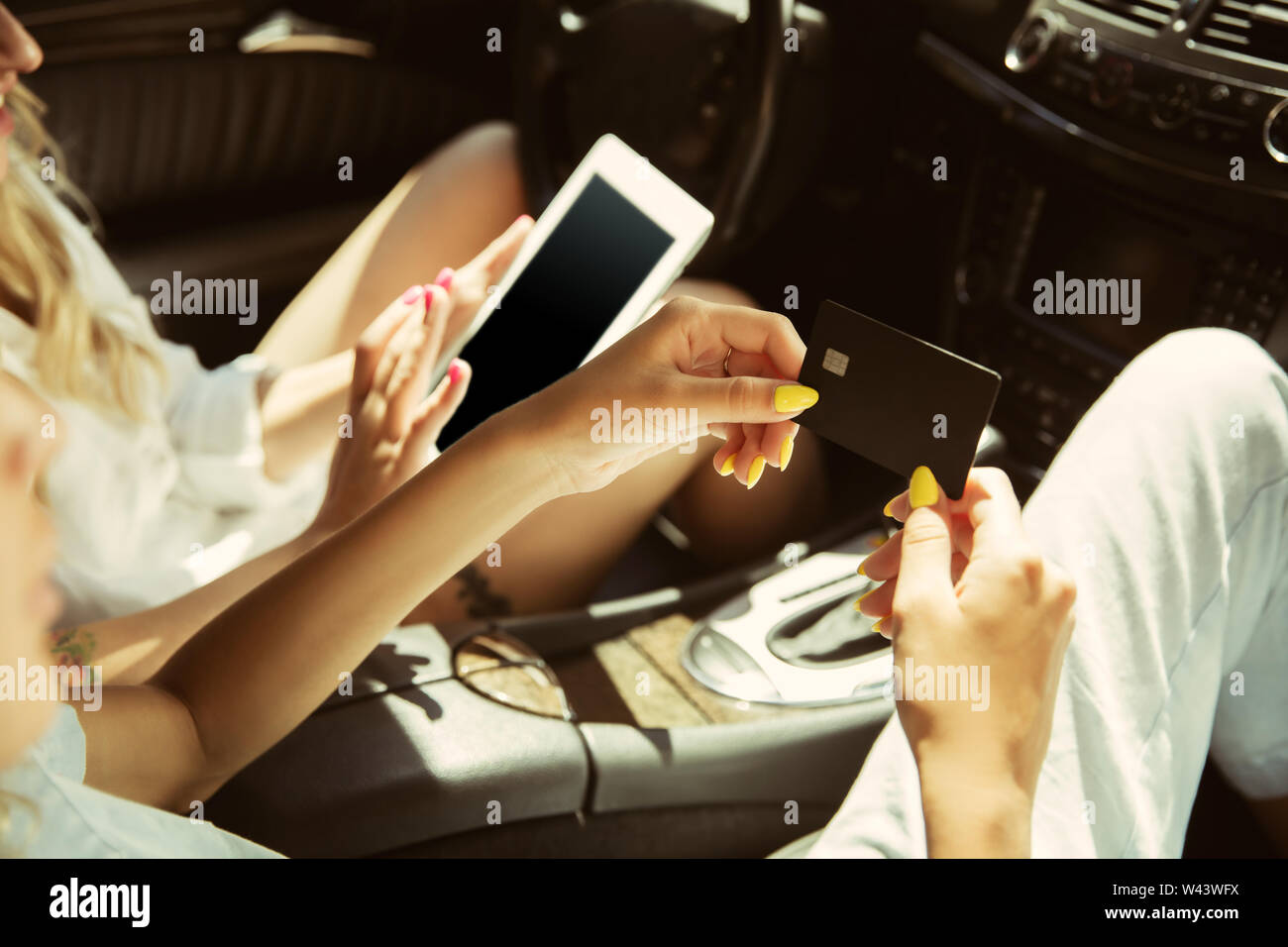 Young lesbian's couple preparing for vacation trip on the car in sunny day. Women sitting and ready for going to sea, riverside or ocean. Concept of relationship, love, summer, weekend, honeymoon. Stock Photo