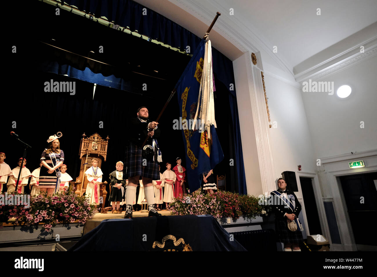 Innerleithen, UK. 19th July, 2019. St Ronans Cleikum Innerleithen Standard Bearer 2019, Ronan D Caine during his installation at the Cleikum Ceremonies in Memorial Hall, Innerleithen. as part of St RonanÕs Games Week, Friday 19 July 2019 . Instituted in 1827, The Games are the oldest organised sports meeting in Scotland and are now part of a week long festival that incorporates many events for every age group. Central to the festivities are the Cleikum Ceremonies when the town's association with its Patron Saint, St. Ronan, is celebrated ( Credit: Rob Gray/Alamy Live News - Stock Image