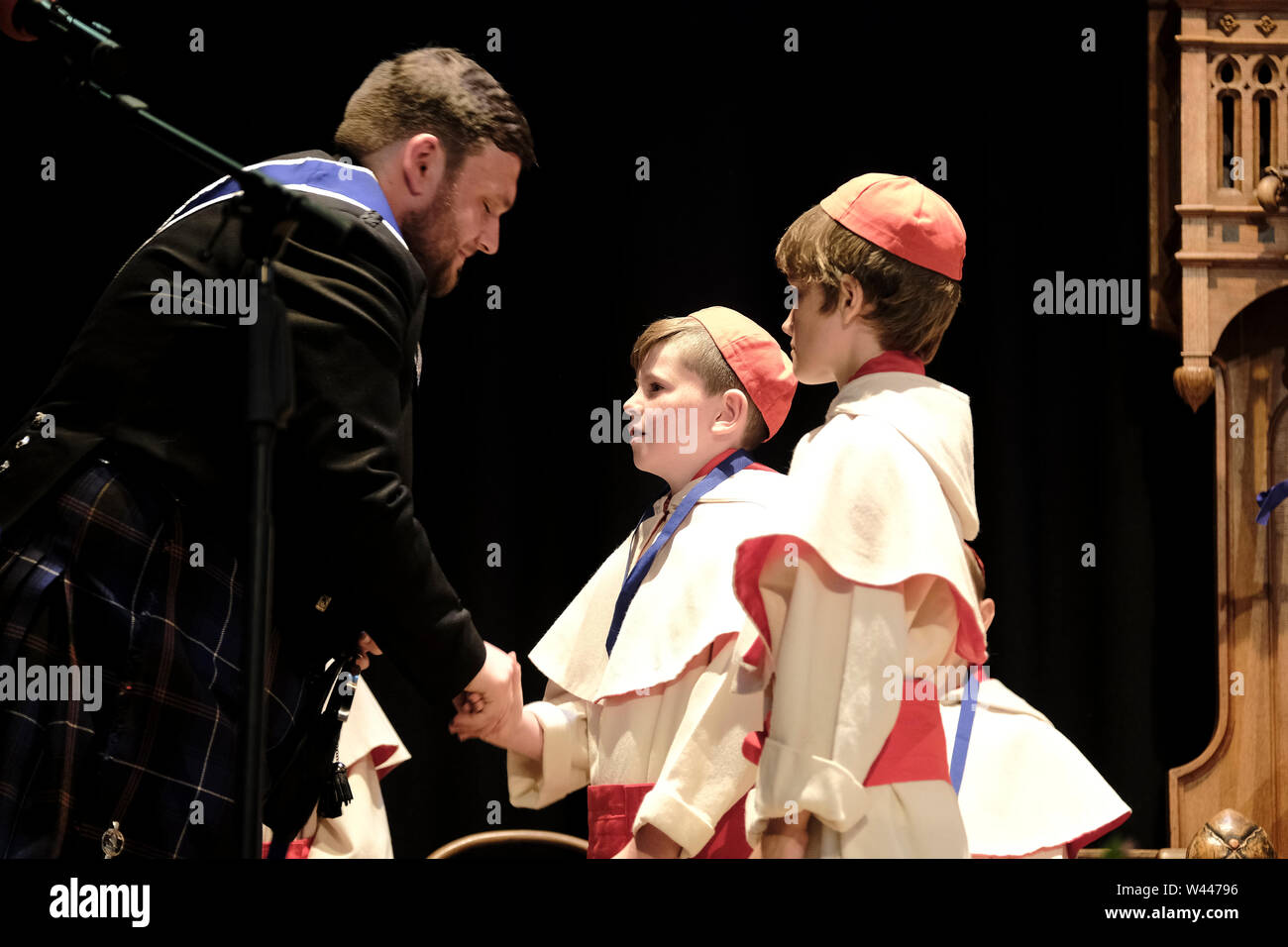 Innerleithen, UK. 19 July 2019. St Ronans Cleikum Innerleithen Standard Bearer 2019, Ronan D Caine during his installation presents Medals to the Monks at the Cleikum Ceremonies in Memorial Hall, Innerleithen. as part of St RonanÕs Games Week, Friday 19 July 2019 . Instituted in 1827, The Games are the oldest organised sports meeting in Scotland and are now part of a week long festival that incorporates many events for every age group. Central to the festivities are the Cleikum Ceremonies when the town's association with its Patron Saint, St. Ronan, is celebrated (Credit: Rob Gray ) - Stock Image