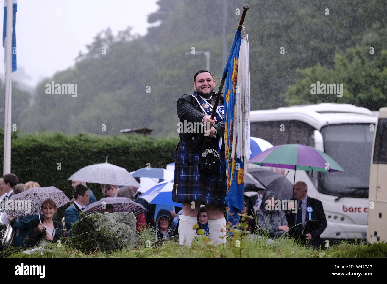 Innerleithen, UK. 19th July, 2019. St Ronans Cleikum Innerleithen Standard Bearer 2019, Ronan D Caine smiling despite the heavy rain at the Cleikum Ceremonies, Memorial Hall, Innerleithen. as part of St RonanÕs Games Week, Friday 19 July 2019 . Instituted in 1827, The Games are the oldest organised sports meeting in Scotland and are now part of a week long festival that incorporates many events for every age group. Central to the festivities are the Cleikum Ceremonies when the town's association with its Patron Saint, St. Ronan, is celebrated ( Credit: Rob Gray/Alamy Live News - Stock Image