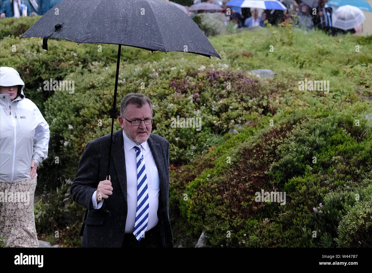 Innerleithen, UK. 19th July, 2019. St Ronans Cleikum David Mundell, Secretary of State for Scotland shelters from the rain at the Cleikum Ceremonies in Memorial Hall, Innerleithen. as part of St RonanÕs Games Week, Friday 19 July 2019 . Instituted in 1827, The Games are the oldest organised sports meeting in Scotland and are now part of a week long festival that incorporates many events for every age group. Central to the festivities are the Cleikum Ceremonies when the town's association with its Patron Saint, St. Ronan, is celebrated ( Credit: Rob Gray/Alamy Live News - Stock Image