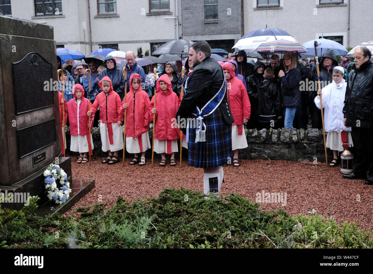 Innerleithen, UK. 19th July, 2019. St Ronans Cleikum Innerleithen Standard Bearer 2019, Ronan D Caine lays a wreath at the war memorial at the Cleikum Ceremonies, Memorial Hall, Innerleithen. as part of St RonanÕs Games Week, Friday 19 July 2019 . Instituted in 1827, The Games are the oldest organised sports meeting in Scotland and are now part of a week long festival that incorporates many events for every age group. Central to the festivities are the Cleikum Ceremonies when the town's association with its Patron Saint, St. Ronan, is celebrated ( Credit: Rob Gray/Alamy Live News - Stock Image