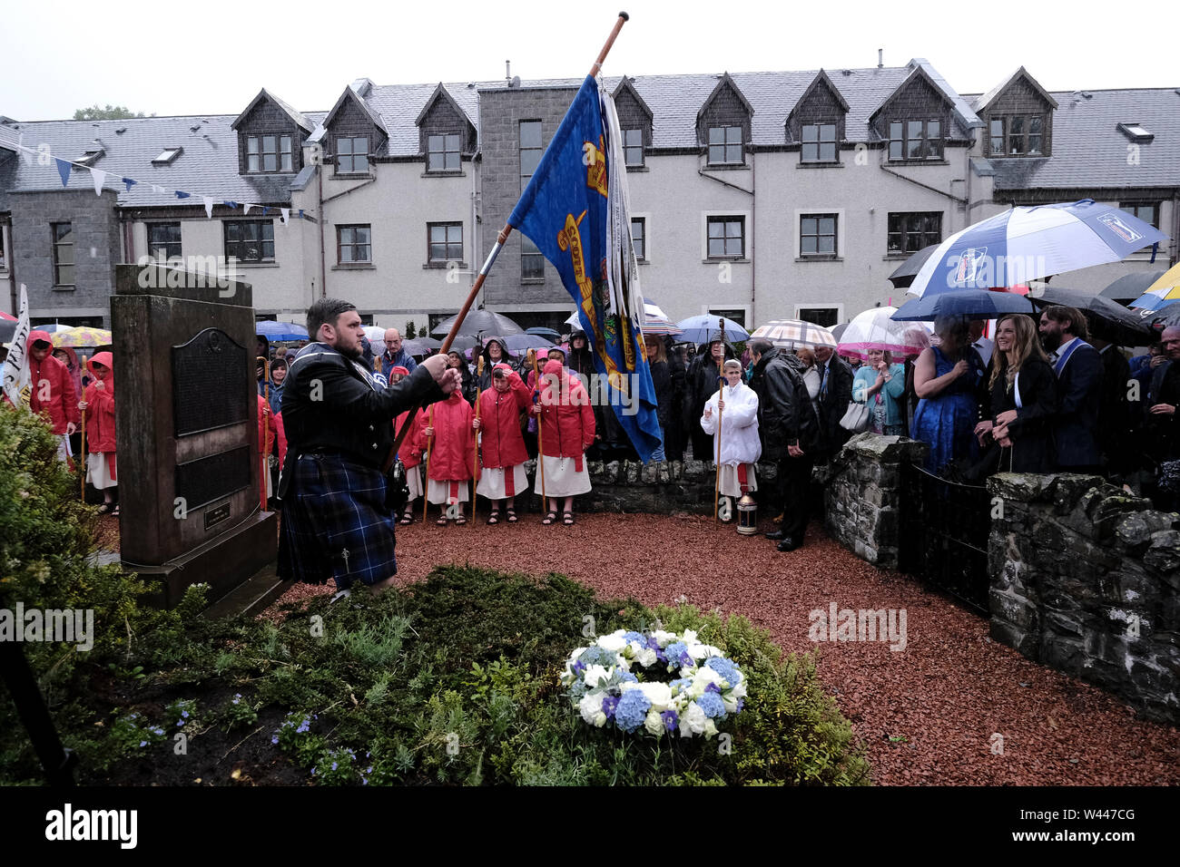 Innerleithen, UK. 19th July, 2019. St Ronans Cleikum Innerleithen Standard Bearer 2019, Ronan D Caine walks towards the war memorial at the Cleikum Ceremonies, Memorial Hall, Innerleithen. as part of St RonanÕs Games Week, Friday 19 July 2019 . Instituted in 1827, The Games are the oldest organised sports meeting in Scotland and are now part of a week long festival that incorporates many events for every age group. Central to the festivities are the Cleikum Ceremonies when the town's association with its Patron Saint, St. Ronan, is celebrated ( Credit: Rob Gray/Alamy Live News - Stock Image