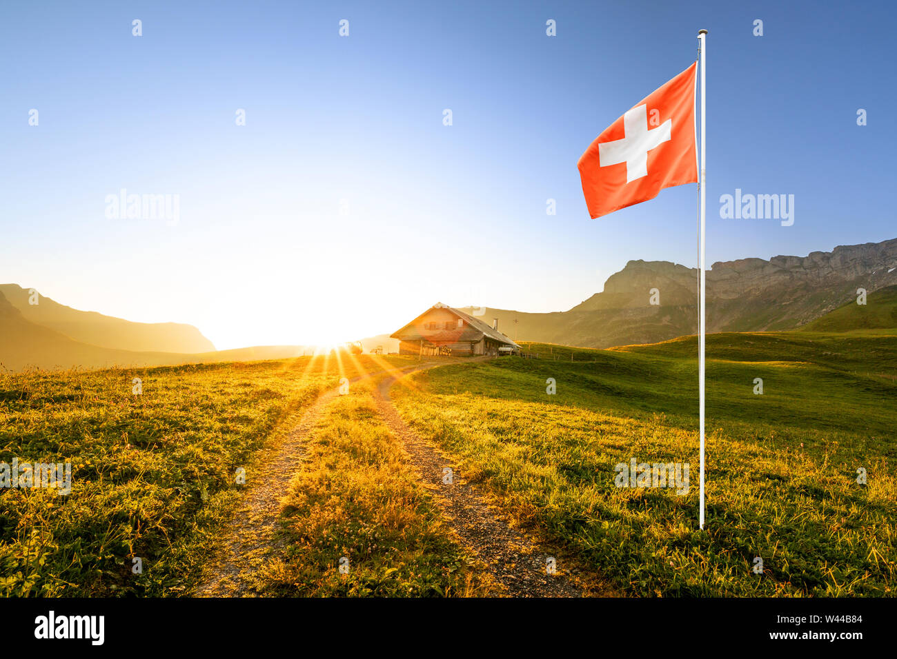 small road leading to a swiss chalet or farm in a mountain landscape at sunrise with sun star and a waving swiss flag in the foreground Stock Photo