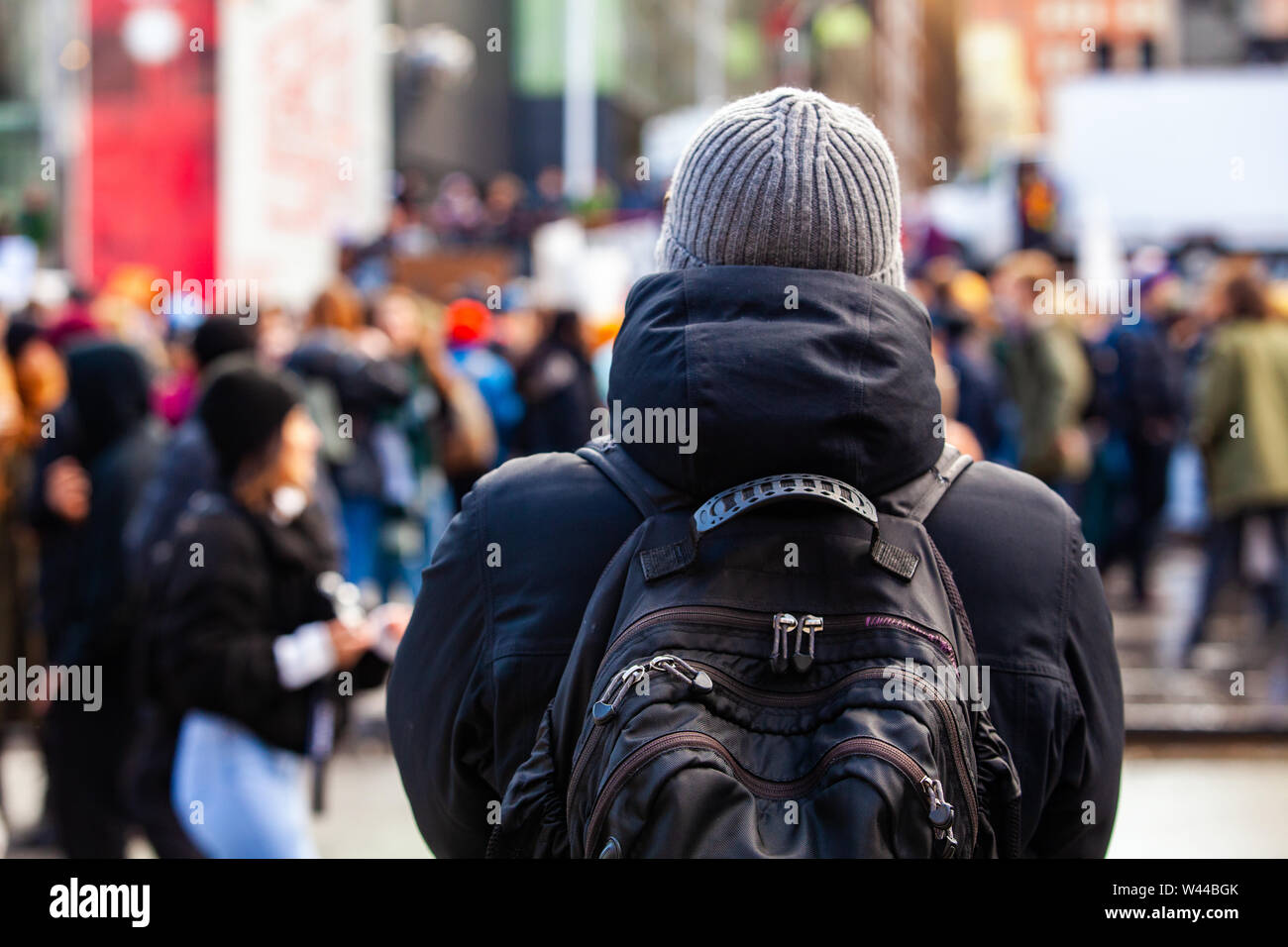 A man wearing a backpack is viewed from behind, as a large crowd of environmentalists is seen blurry in the background. with room for copy Stock Photo
