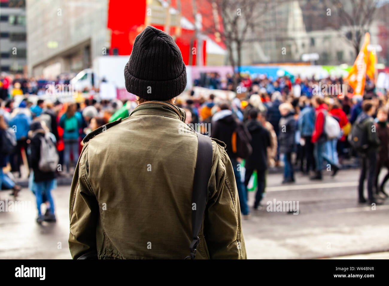 A young man is seen from the back, wearing an olive jacket and wooly hat, as eco-activists march against global warming in a blurry background. Stock Photo