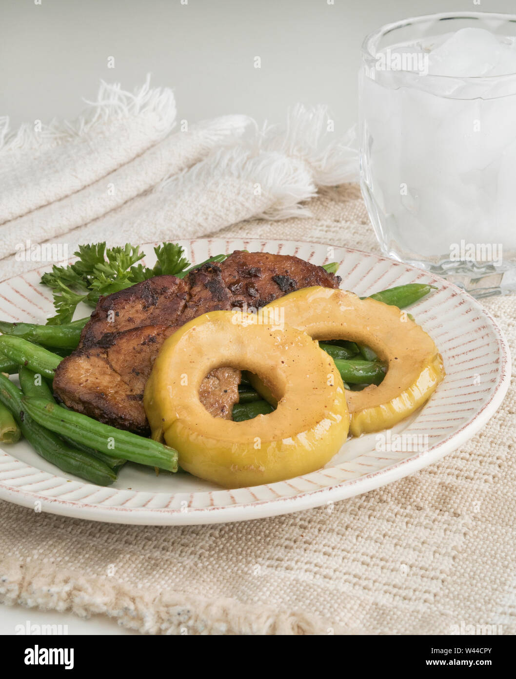 Individual serving of garlic green beans topped with seasoned meat medallions and glazed apple rings Stock Photo