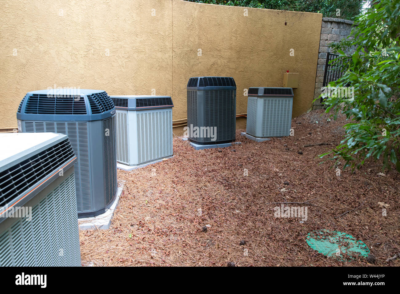 Multiple Air Conditioner Compressors next to large house or building, with room for copy space Stock Photo