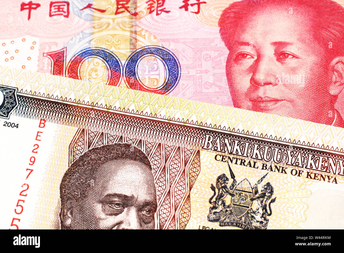 A fifty Kenyan shilling note, in macro, close up with a red one hundred yuan renminbi note featuring a portrait of Mao Tse Tung Stock Photo