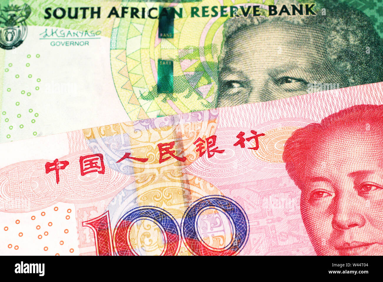A green ten rand note from South Africa close up in macro with a red one hundred yuan renminbi bank note from the People's Republic of China Stock Photo