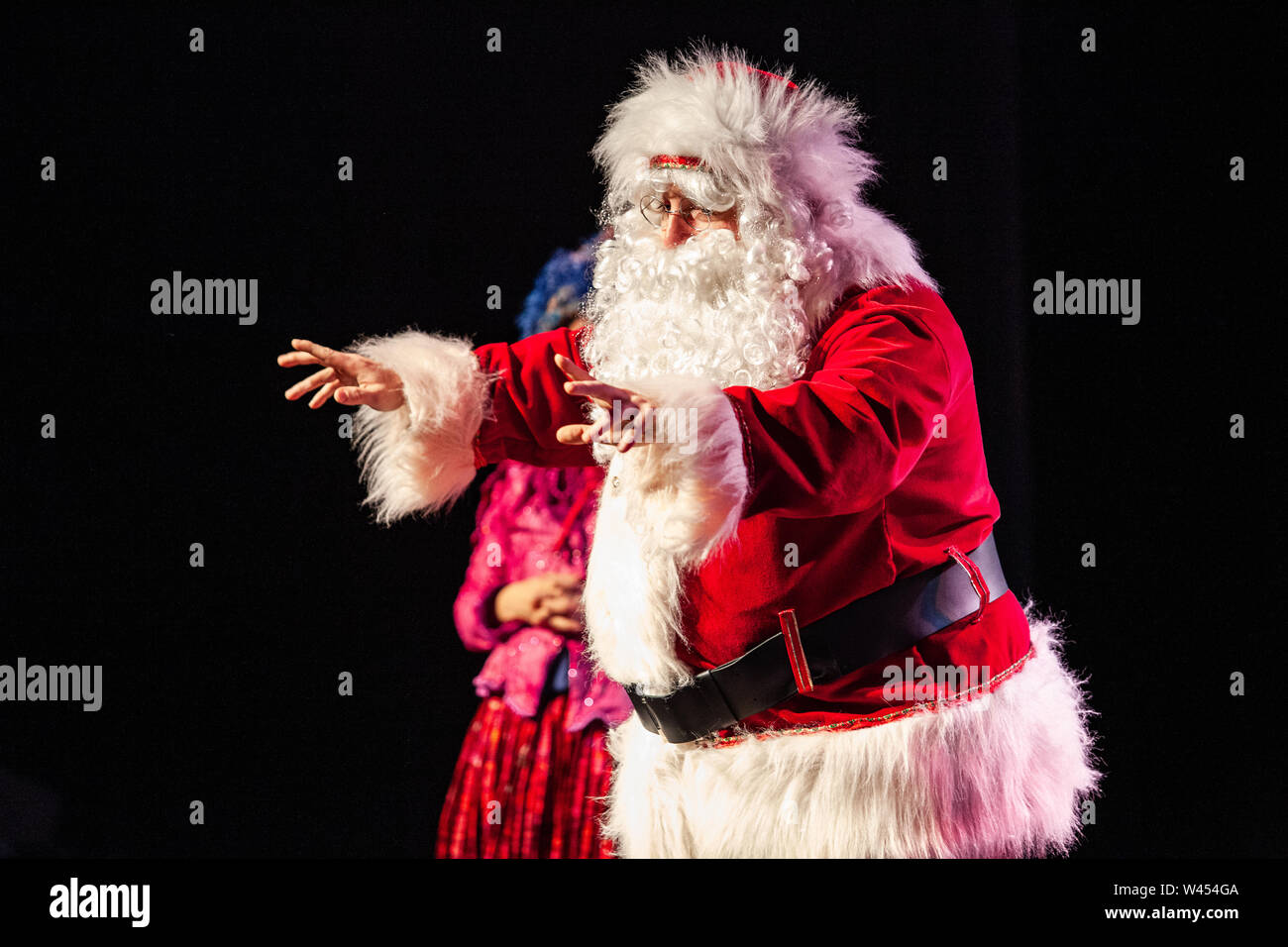 A large man dressed in a Saint Nicholas costume is seen reaching his arms out in front to address youngsters at a christmas festival, against a black background Stock Photo