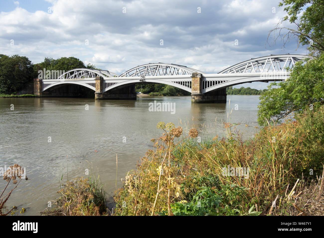 The River Thames flowing peacefully under Joseph Locke's Barnes Railway Bridge, Barnes, London, UK Stock Photo